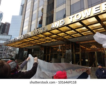 New York City, New York / USA - January 20 2018: As Women's March demonstrators pass the Trump International Hotel & Tower, many hold their banners towards those allowed on the sidewalk.