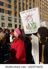 """New York City, New York / USA - January 20 2018: At the NYC Women's March, a demonstrator carries a sign with an image of an angry Statue of Liberty ready to fight captioned, """"Girl, Hold My Earrings""""."""