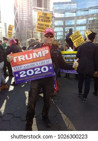 "New York City, New York / USA - January 20 2018: Trump supporter with a ""Re-Elect Donald J. Trump, Keep America Great! 2020"" sign during the NYC Women's March. Under the brim of his hat, a camera."