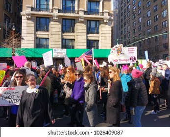 """New York City, New York / USA - January 20 2018: Women's March: A woman wears a judge's robe while another's sign quotes Martin Luther King Jr., """"Injustice anywhere is a threat to justice everywhere."""""""