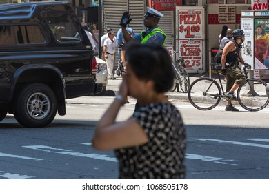 """NEW YORK CITY, USA – JULY 16, 2013: A policeman regulating the traffic of pedestrians and cars at the intersection of 6th Avenue and W38th street during a public event """"MLB all stars game"""" in New York"""