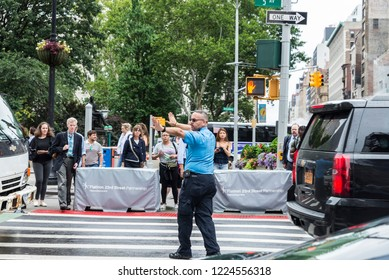 New York City, USA - July 25, 2018: Police stopping the traffic raising their hands so that the people pass in Fifth Avenue in Manhattan in New York City, USA