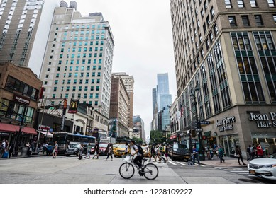 New York City, USA - July 25, 2018: Sixth Avenue (6th Avenue) – officially Avenue of the Americas - with people and cyclist around and traffic in Manhattan in New York City, USA