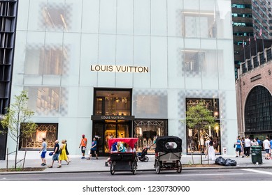 New York City, USA - July 28, 2018: Louis Vuitton, luxury clothing store, in Fifth Avenue (5th Avenue) with people around in Manhattan in New York City, USA