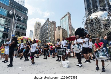 New York City, USA - July 25, 2018: Performance of a group of dancers and percussionists in the street in front of Trump International Hotel and Tower with people in Manhattan in New York City, USA