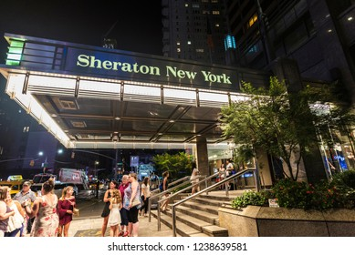 New York City, USA - July 28, 2018: Sheraton New York Times Square Hotel at night on Seventh Avenue (7th Avenue) next to Times Square with people around in Manhattan in New York City, USA
