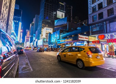 New York City, USA - July 28, 2018: Taxi and shops at night on Seventh Avenue (7th Avenue) next to Times Square with people around in Manhattan in New York City, USA