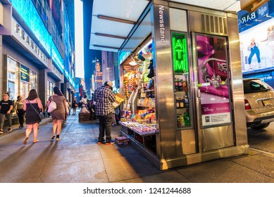New York City, USA - July 30, 2018: Newsstand at night on Seventh Avenue (7th Avenue) next to Times Square with people around in Manhattan in New York City, USA