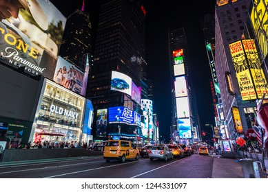 New York City, USA - July 30, 2018: Times Square at night with people around and large advertising screens in Manhattan in New York City, USA