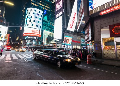 New York City, USA - July 30, 2018: Luxury black limousine on Times Square at night with people around and large advertising screens in Manhattan in New York City, USA