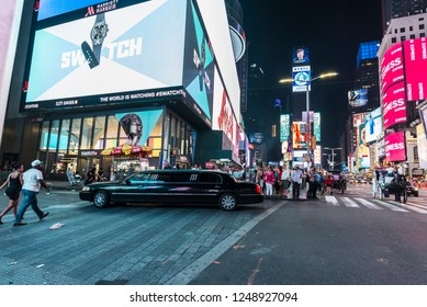 New York City, USA - July 30, 2018: Black luxury limousine on Times Square at night with people around and large advertising screens in Manhattan in New York City, USA