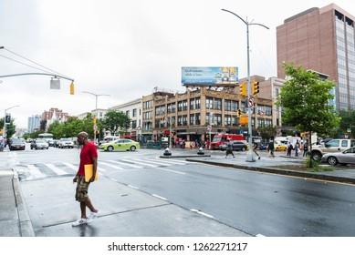 New York City, USA - July 25, 2018: Traffic on Malcolm X Boulevard with people around in Harlem, Manhattan, New York City, USA