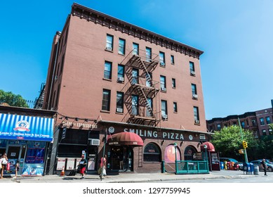 New York City, USA - July 26, 2018: Street with restaurants, shops and subway station with people around in Brooklyn, Manhattan, New York City, USA