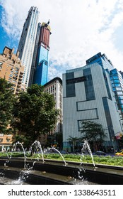 New York City, USA - July 28, 2018: Fountain in Columbus Circle and Central Park Tower, also known as the Nordstrom Tower, in construction with people around in Manhattan, New York City, USA