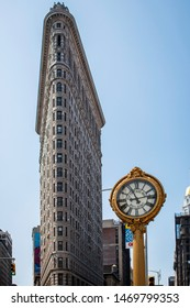 New York City, New York, USA - July 27, 2019: Dramatic architecture of Flatiron Building In Manhattan With Ornate gold clock and sunny blue sky