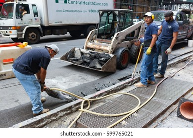 New York City, Usa - July 08, 2015: Construction site with workers on the street in Midtown Manhattan. Urban maintenance is constantly in action in the city.