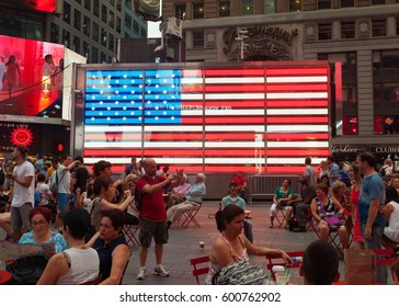 New York City, Usa - July 09, 2015: Tourists in front of an electronic American Flag which adorns the sides of the Armed Forces Recruitment booth in Times Square.