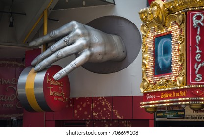 NEW YORK CITY, USA – JULY 13, 2013: A large hand above the sign of Madame Tussaud at the entrance to the museum in Times Square in New York on a summer day.