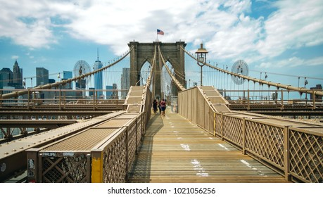 NEW YORK CITY, USA - JUNE 21, 2016: Pedestrians walking by Brooklyn Bridge with Manhattan skyline on background, in New York City