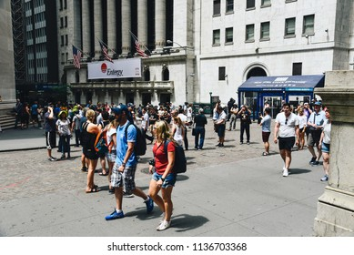New York City, USA - June 20, 2018: A crowd of people in Wall Street in front of New York Stock Exchange and Federal Hall buildings
