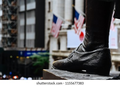 New York City, USA - June 20, 2018: Close up of foot  of George Washington statue in Federal Hall against New York Stock Exchange building in Wall Street in Financial District. Selective focus