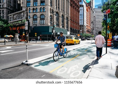 New York City, USA - June 20, 2018: Cyclist riding on bike lane in Park Row in Financial District