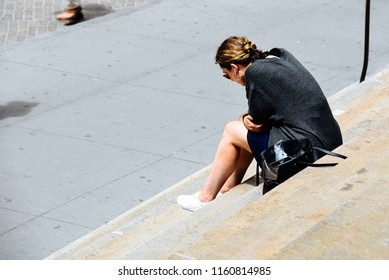New York City, USA - June 20, 2018: Unidentified woman with headsets sitting on the steps of Federal Hall building in Wall Street
