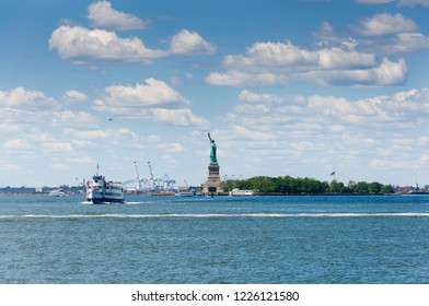 New York City, USA - June 7, 2010: View of the Statue of Liberty in New York City, with tourist boats in the Hudson River.