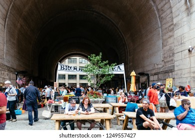 New York City, USA - June 24, 2018: Brooklyn Flea Market in DUMBO. It includes vendors of furniture, vintage clothing, collectibles and antiques, jewelry, art, and crafts by local artisans.