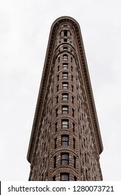 New York City, USA - June 20, 2018: Flatiron Building  in Manhattan. Low angle view against cloudy day. It is one of the worlds most iconic skyscrapers and a symbol of New York