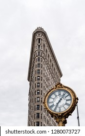 New York City, USA - June 20, 2018: Flatiron Building in Manhattan. Low angle view against cloudy day with clock on foreground. It is one of the worlds most iconic skyscrapers.