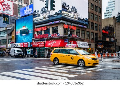 New York City, USA - June 21, 2018: Street scene in Seventh Avenue in Manhattan with taxi cab and popular restaurant Hooters
