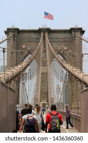 New York City, USA - June 05, 2019: Tourists and locals walking across famous landmark Brooklyn bridge to cross the river. It connects the boroughs of Manhattan and Brooklyn, spanning the East River.