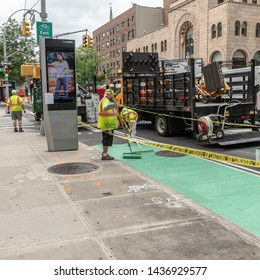 New York City / USA - June 17th 2019 - City workers painting bike lane with green paint for cycling