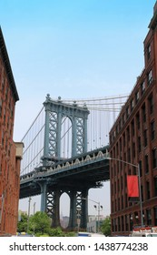New York City, USA - June 05, 2019: Famous Manhattan bridge in New York without people on street with old architecture shot from Brooklyn DUMBO neighborhood in New York City.