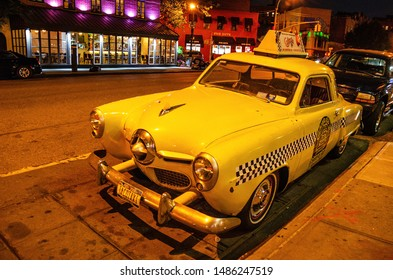NEW YORK CITY, USA -  JUNE, 2016: 1950 Studebaker yellow taxi outside the Caliente Cab restaurant on Seventh Avenue South in Greenwich Village in New York City