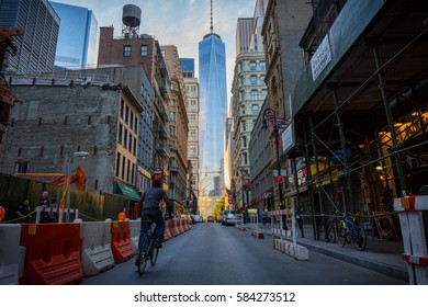 New York City, USA - June 13, 2015: Fulton street in New York City with a man riding a bicycle and a view of the One World Trade Center complex of Lower Manhattan, New York City.