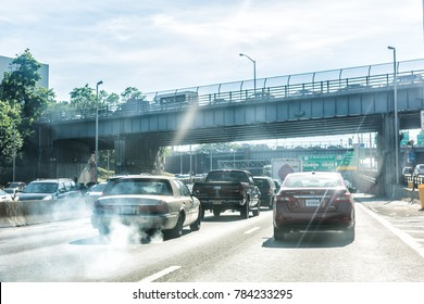 New York City, USA - June 11, 2017: Road and street highway in NYC with sign for George Washington Bridge, smoke coming out of exhaust pipe of car