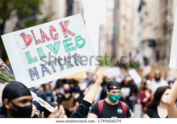 New York City, New York / USA - June 5 2020. Protests in New York. People with protesting posters marching protest over George Floyd death. Black lives matter movement in New York.