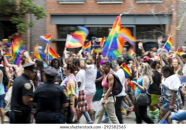 NEW YORK CITY, USA - JUNE 28, 2015: Celebrants at the annual gay pride parade wave rainbow flags as they pass in front of cheering spectators on Gay Street, in Greenwich Village.