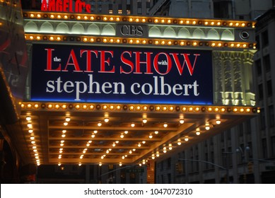 New York City, USA - March 10 2018: Manhattan NYC buildings in Times Square, Broadway street avenue road, signs for Colbert Late Show, Angelo's Pizza Italian restaurant, Marquee / Theatre at Night