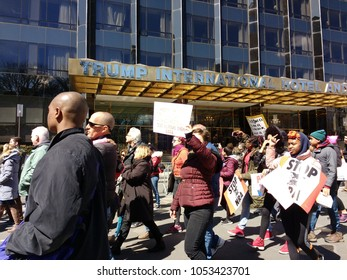 New York City, New York / USA - March 24 2018: Protesters give the finger as they pass the Trump International Hotel & Tower during the March for Our Lives in New York City.