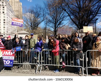 New York City, New York / USA - March 24 2018: Spectators, including Trump supporters, behind barricades on Columbus Circle during the March for Our Lives in New York City.
