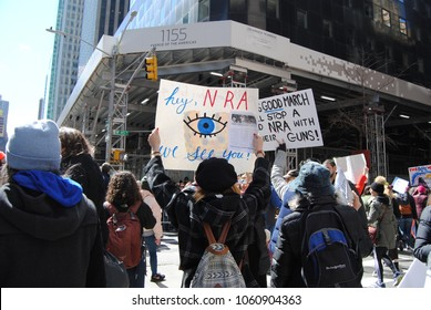"New York City, New York / USA - March 24 2018: A protester carries a sign with one eye that says, ""Hey, NRA We See You!"" during the March for Our Lives in New York City."
