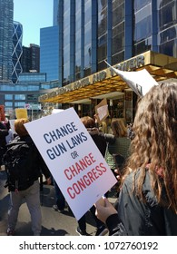 """New York City, New York / USA - March 24 2018: March for Our Lives: A protester walks by the Trump International Hotel & Tower carrying a sign that says, """"Change Gun Laws Or Change Congress""""."""