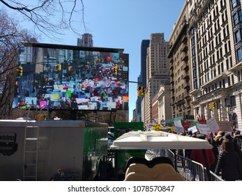 New York City, New York / USA - March 24 2018: A large-screen television on Central Park West broadcasts demonstrators marching during the March for Our Lives in New York City.