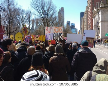 """New York City, New York / USA - March 24 2018: Among the demonstrators on Central Park West during the March for Our Lives, someone holds a sign that says, """"Buy Books Not Guns""""."""