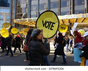 New York City, New York / USA - March 24 2018: Demonstrators carrying shield-like signs encouraging people to vote march by the Trump International Hotel & Tower during the March for Our Lives.