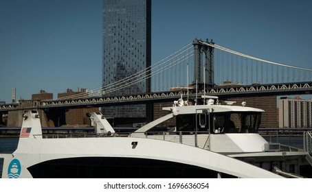 NEW YORK CITY, USA - March 28 2020 : Metropolitan Transit Authority ferries passing each other near the Brooklyn Bridge, as it heads to Manhattan from Brooklyn during the Coronavirus outbreak