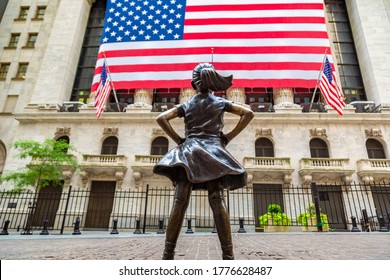 NEW YORK CITY, USA - MARCH 15, 2020:  Fearless Girl Statue looking up at  New York Stock Exchange building at Wall Street in Manhattan, New York City, USA